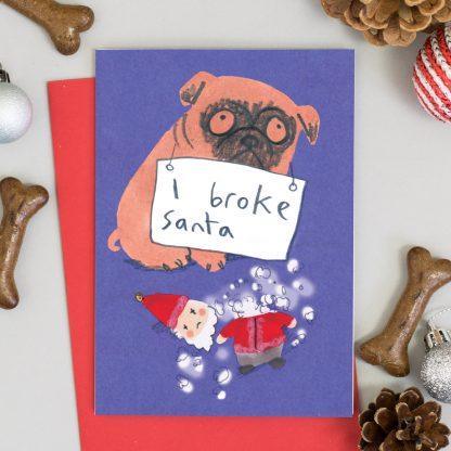 pug with broken santa toy and sign around neck reading 'I broke santa' Dog Christmas Card