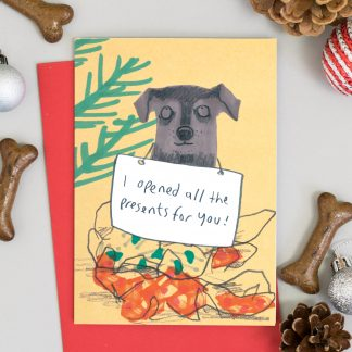 Black dog sitting on wrapping paper of opened presents Dog Christmas Card